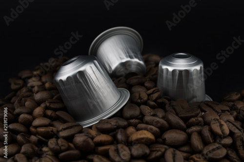 Wall Murals Cafe Italian coffee capsules or coffee pods on coffee beans, black background.
