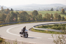 Bearded Motorcyclist In Helmet, Sunglasses And Black Leather Clothing Riding Bike Along Sharp Turn Of Empty Road On Bright Summer Day On Misty Background Of Rural Landscape And Distant Green Hills.