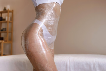Body wrapping in a spa room. Anti cellulite fat burning procedure in massage salon for perfect slim body and clear skin