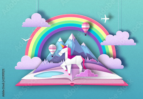 Open fairy tale book with unicorn, rainbow and mountain landscape. Cut out paper art style design