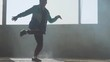 Experienced young hip-hop street dancer performing in front of large window in the dark abandoned building. The man making moves, jumping and crouches dancing.. Slow motion