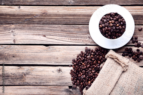 Fotografie, Obraz  Coffee beans with sackcloth and cup on brown wooden table