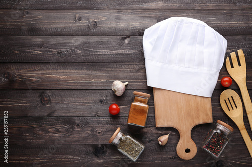 Chef hat with spices in jars and vegetables on wooden table
