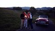 Two senior couples with sparklers standing by cabriolet on a road trip at dusk.