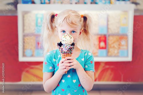 Fotografie, Obraz  Cute adorable Caucasian blonde preschool girl child with blue eyes holding ice cream in large waffle cone with sprinkles