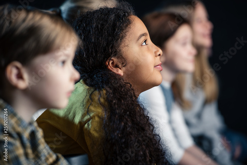 Fotografia  selective focus of african american girl watching movie in cinema with friends