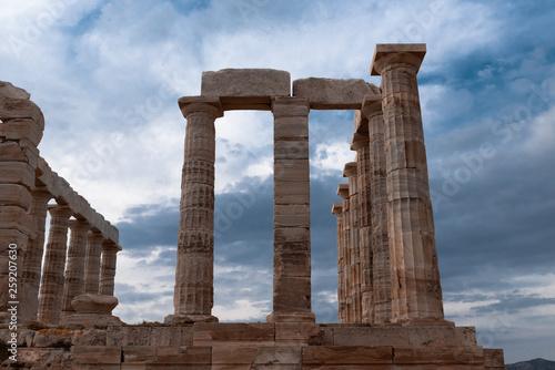 Fotografia  Greek temple ancient stones orange clouds blue sky