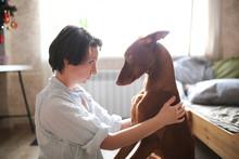 Woman Hugs Pharaoh's Dog On Floor In Apartment