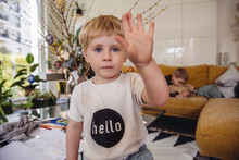 Boy At Home Holding Up Hand To Say Hello