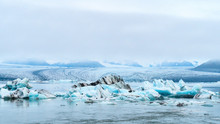 Luminous Blue Icebergs  Floating In Jokulsarlon Glacial Lagoon With Background Of Glacier Mountain. South Iceland, Vatnajökull National Park. Copy Space Background. Place For Text.