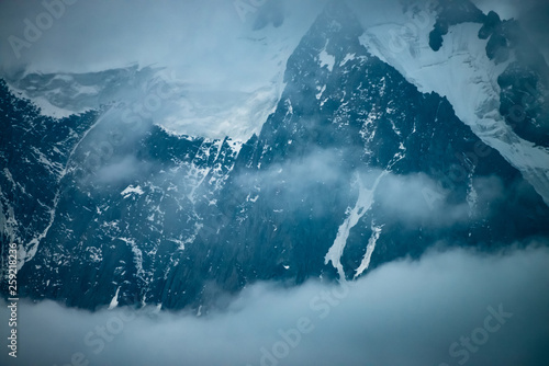 Fototapety, obrazy: Low cloud before huge glacier. Giant snowy rocky mountain wall in thick fog. Early morning in mountains. Impenetrable fog. Dark atmospheric foggy landscape with cold rocks. Tranquil mystic atmosphere.