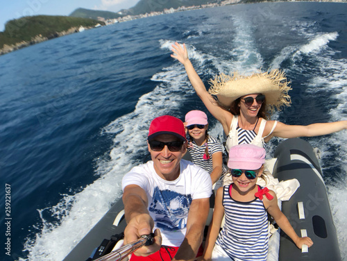 Fotografia family with children sailing on an inflatable motorboat in the sea