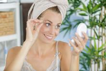 Young Woman Plucking Eyebrow With Tweezers
