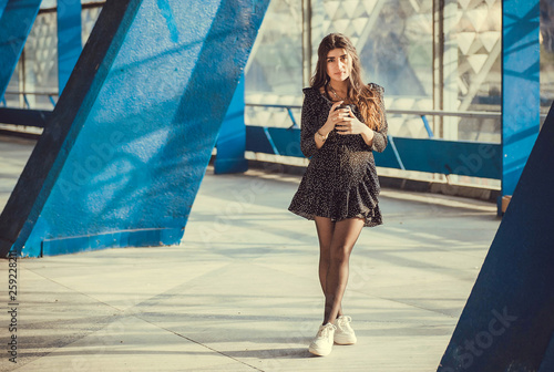 obraz dibond Brunette girl standing between columns of grunge city area. Young woman drinking coffee in urban sunny space