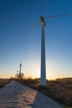 Line Of Wind Turbines Along The Dirt Road At The Sunset