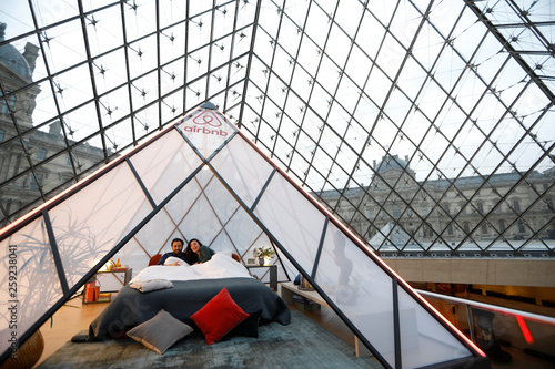 Airbnb employees pose on a bed under the glass Pyramid