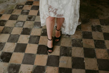 Bride In Black Peep Toe Wedding Shoes And Lace Dress On Old Checkered Tile