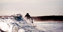 Silhouette Of Surfer On Small Wave