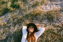 Smiling Japanese Woman Laying In Sand Dune
