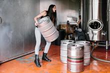 Woman Lifting Keg In Brewery