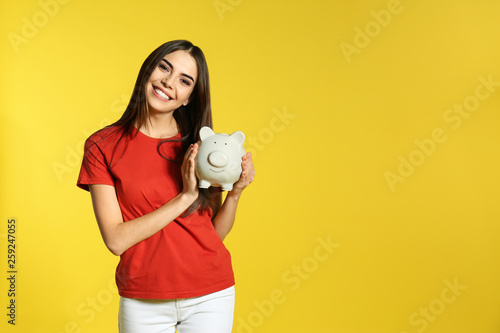 Fototapeta Young woman with piggy bank on color background, space for text. Money saving obraz