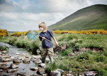 Boy With Fishing Net Standing By Stream In Landscape