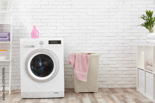 Fotografie, Obraz  Modern washing machine near brick wall in laundry room interior, space for text