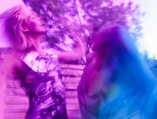 Abstract Motion Blur Of Women Dancing And Having Fun With Harsh Summer Light And Strong Vivid Colours