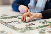 Seniors In Assisted Living Home Working On Jigsaw Puzzle Together