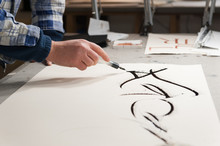 A Master Calligrapher Using A Siringe To Draw Marks On A Paper