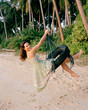 Young woman on tire swing at beach