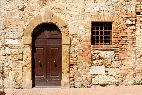 Dark wooden double doors in an ancient stone wall, with a window with bars on it - 259260215
