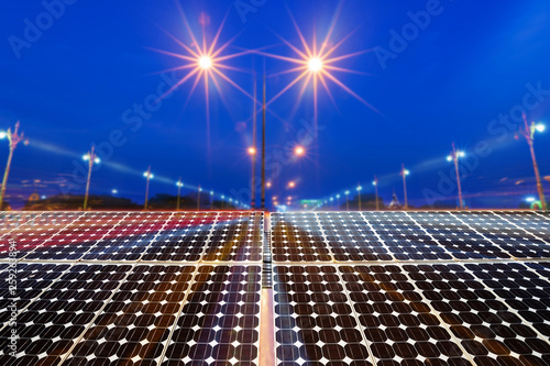 Obraz Texture of photovoltaic panels solar panel with city night light on the Road at night background, Alternative energy concept. - fototapety do salonu