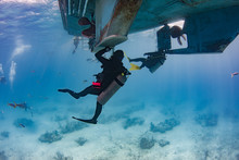 Scuba Divers Hold On To Ropes And The Hull Of The Boat During Their Safety Stop After A Deep Water Dive In The Caribbean
