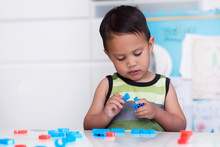 Two Year Old Boy Holding Alphabet Letters Trying To Problem Solve A Spelling Challenge In Preschool.