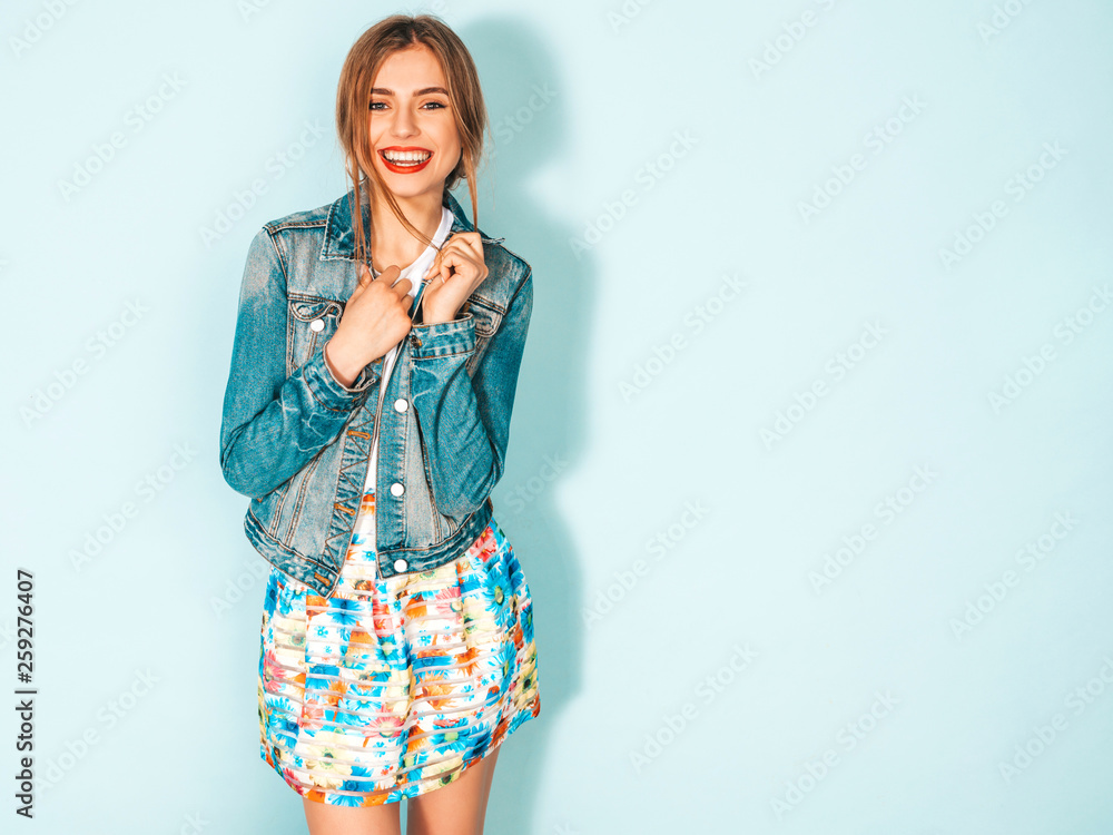Fototapety, obrazy: Portrait of young beautiful smiling hipster girl in trendy summer jeans jacket clothes. Sexy carefree woman posing near blue wall. Positive model having fun