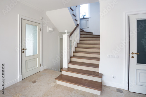 Fotografie, Obraz  wooden spiral staircase in bright interior in vacation house