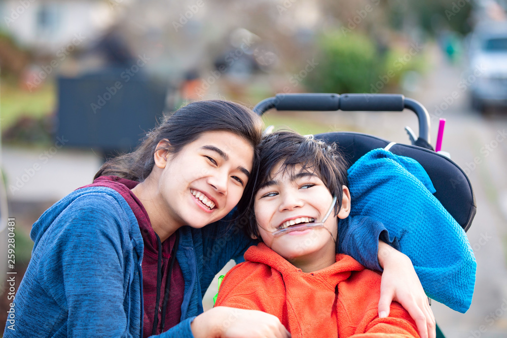 Fototapety, obrazy: Big sister hugging disabled brother in wheelchair outdoors, smiling