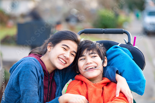 Photo  Big sister hugging disabled brother in wheelchair outdoors, smiling