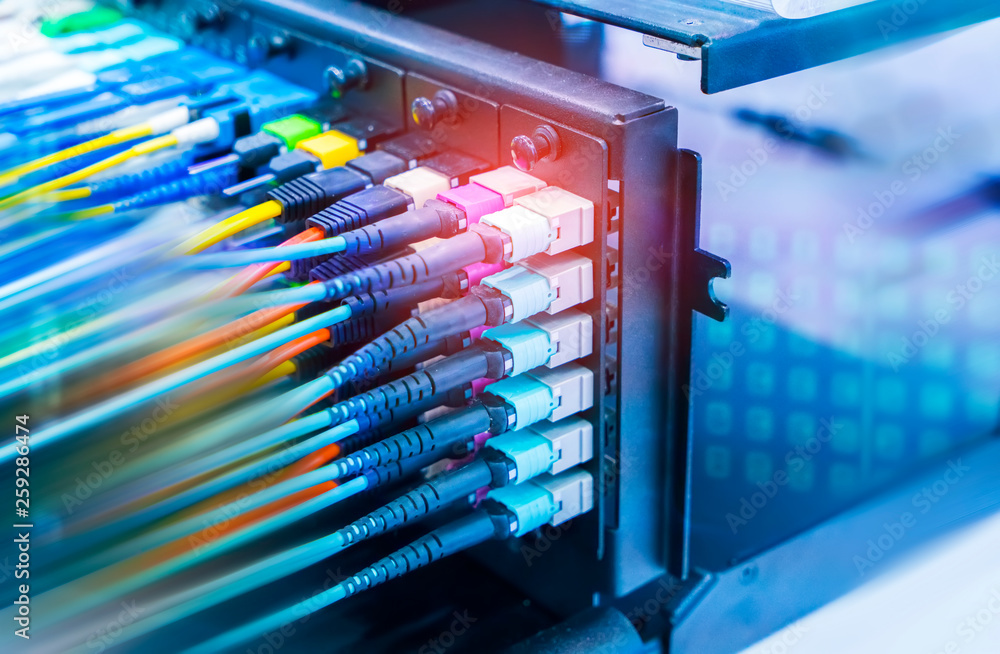 Fototapety, obrazy: optical fiber telecommunication equipment and patchcords inside a network infrastructure.