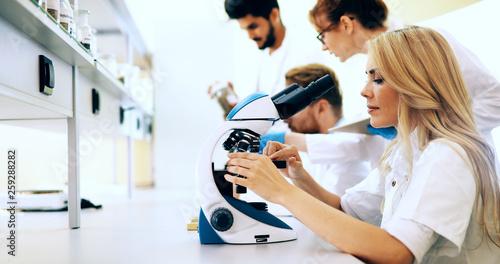 Fotografia  Young scientist looking through microscope in laboratory