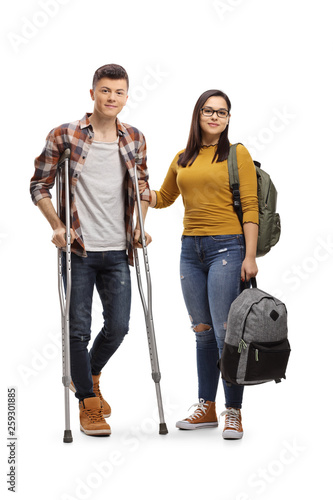 Fotografia Male student with crutches and a female student holding a backpack