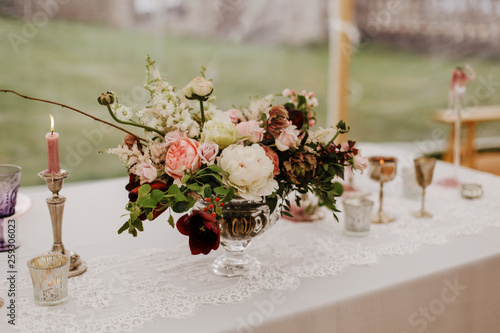 Poster Floral Burgundy, pink and white flowers centerpiece, white lace table linen, burning candles. Elegant wedding, event, dine dinning decor in marquee, outdoor.