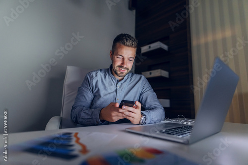 Garden Poster Smiling Caucasian handsome freelancer sitting in office late at night and using smart phone. On desk charts and laptop.