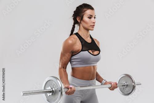 Młody niesamowity silny sport fitness kobieta pozowanie na białym tle nad białym tle zrobić ćwiczenia ze sztangą.