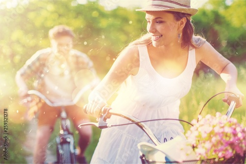 Poster Attraction parc Happy young couple cycling through the park