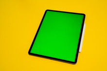 New IPad, Tablet On A Yellow Background With A Keyboard And Pen, And Green Screen Top View