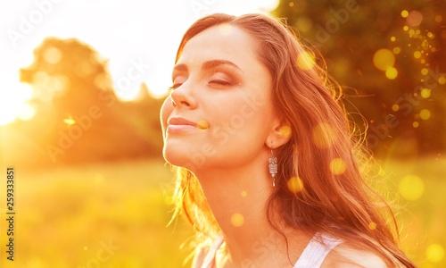 plakat Young woman on field under sunset light