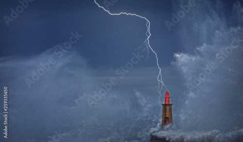 Lightning and wave over old lighthouse. Canvas Print