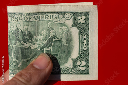 A two-dollar bill in a man's hand against a red background. - 259336249